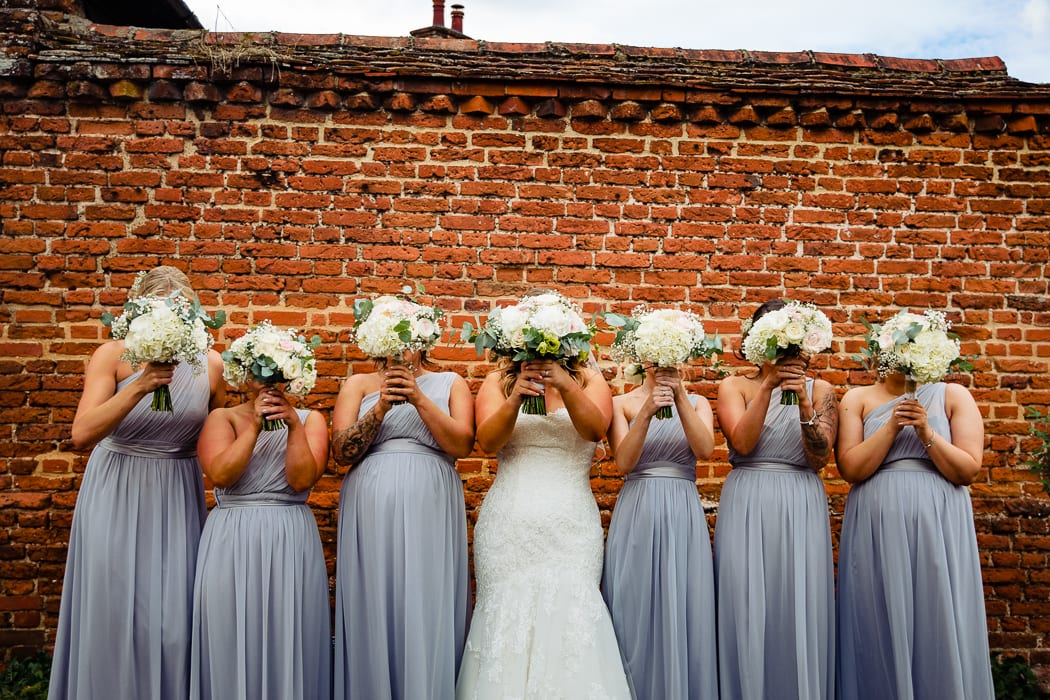 bride and bridesmaids against a brick wall