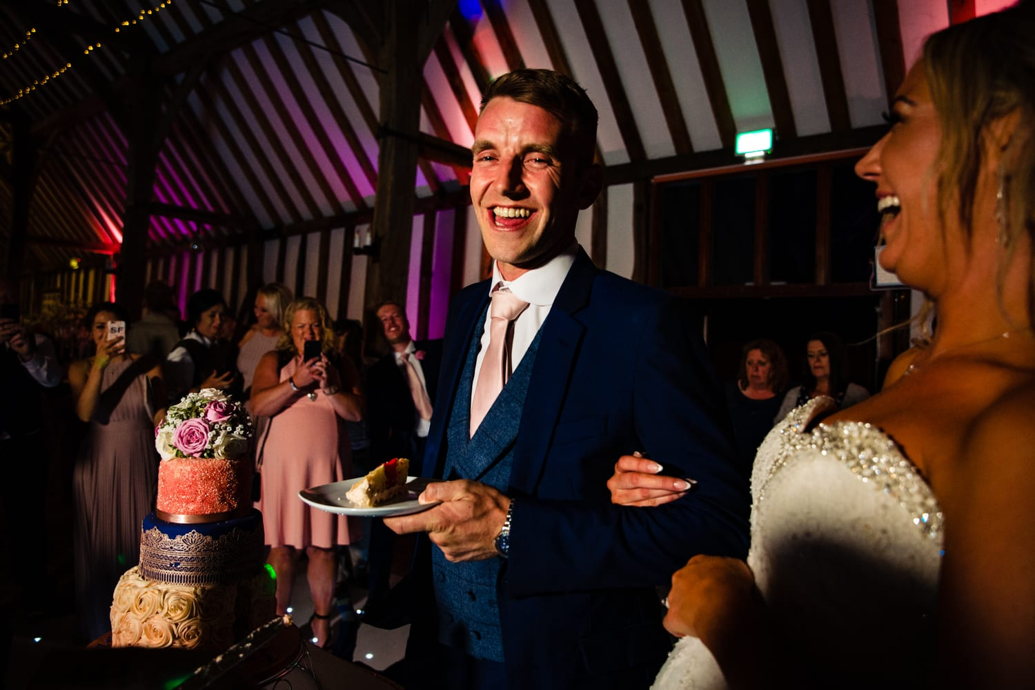 groom holding a slice of cake - wedding photography Essex