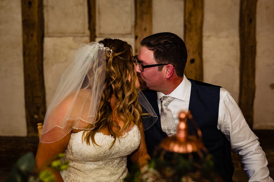 bride and groom signing register - kissing - essex wedding photographer